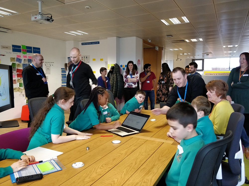Children and NHSBSA colleagues gathered around a large table with a laptop on it.